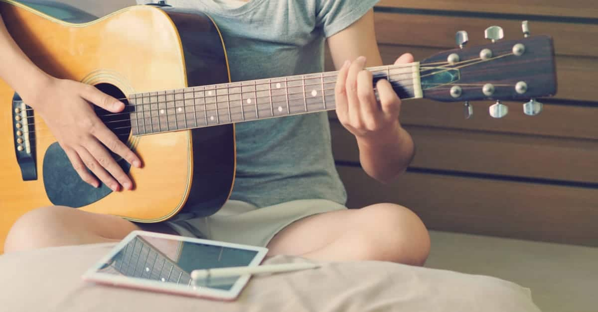 Female guitarist sits down to play an easy song, following from her tablet device.