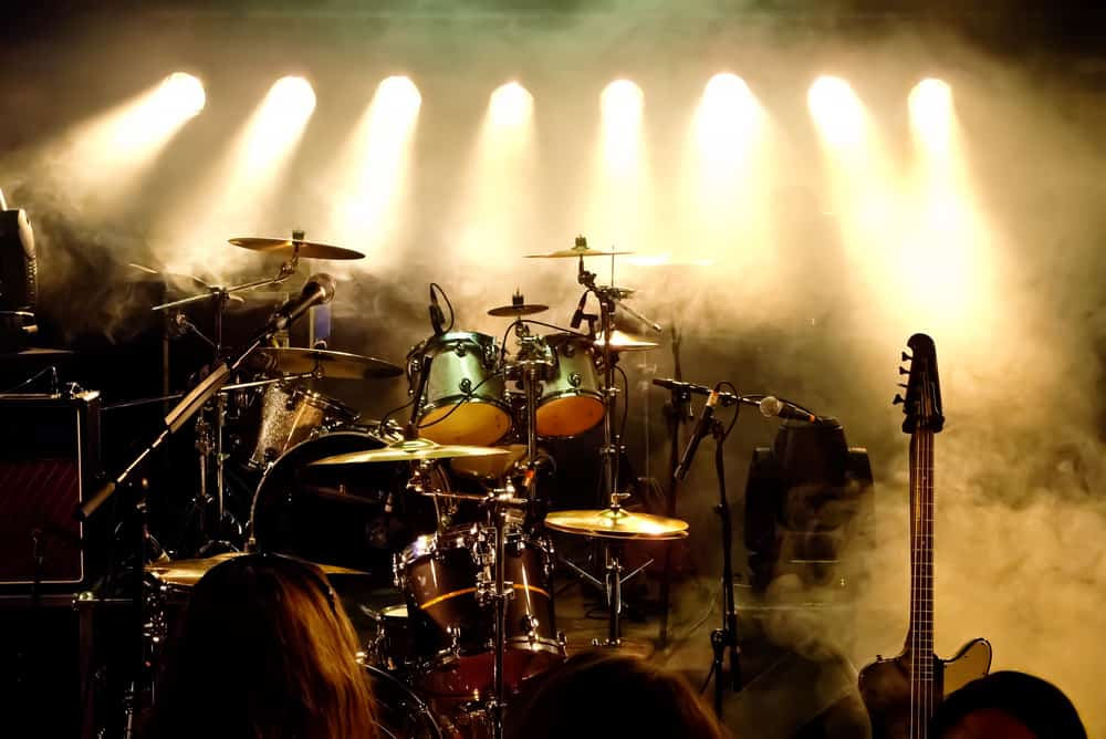 Drum kit and guitar sit on an empty stage before a performance.