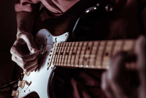 Male guitarist strums his guitar