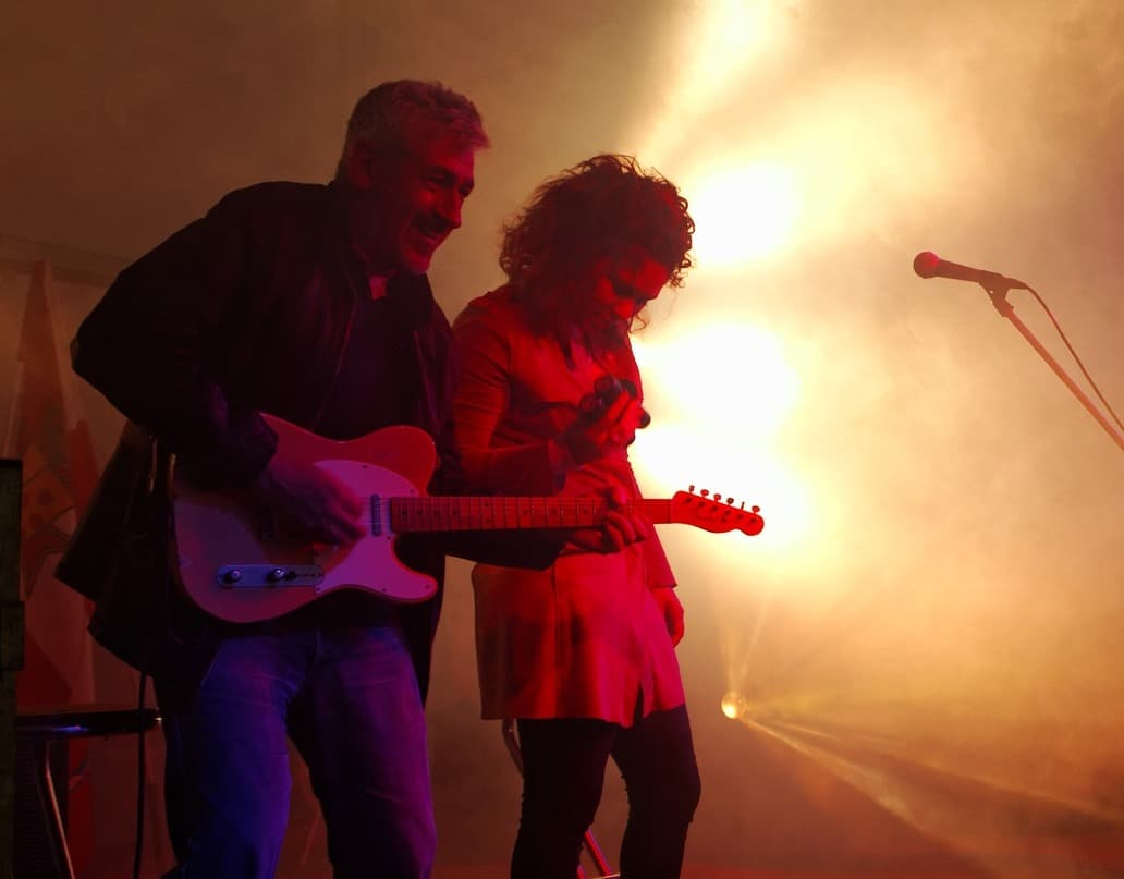 Male guitarist and female vocalist perform as a duo perform on stage.